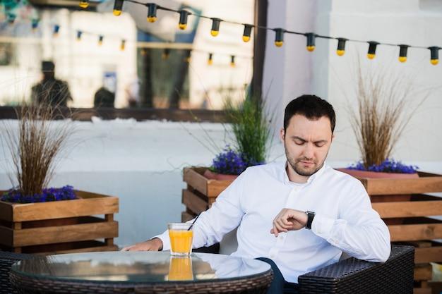 ハンサムな実業家は、カフェテリアでクライアントを待っています。彼は時計に触れ、期待してそれを見ています。