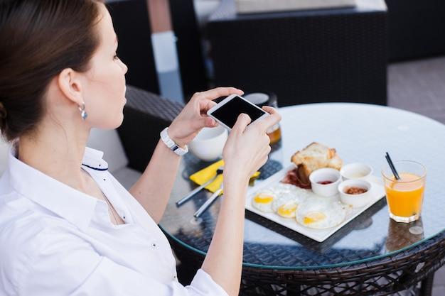 携帯電話で食べ物の写真を撮る女性の手。食べ物の写真。おいしい朝食。