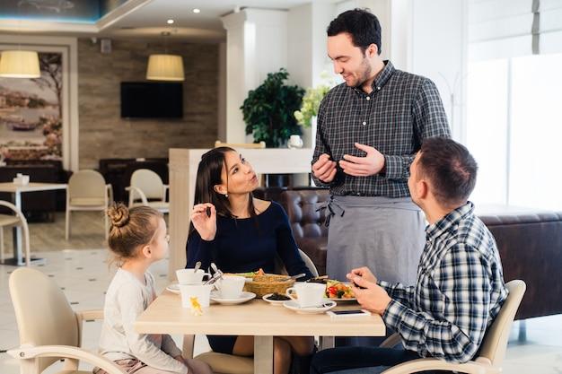 Дружелюбный улыбающийся официант принимает заказ за столом семьи, обедают вместе
