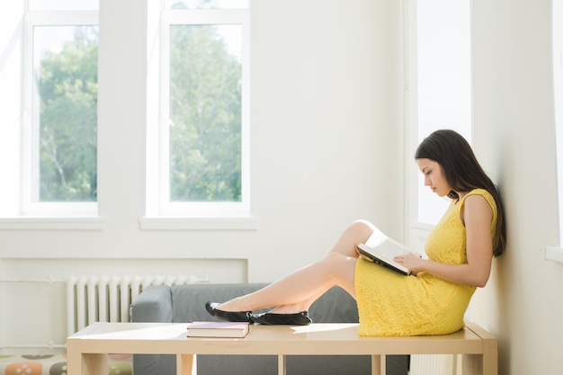 女子学生が試験の準備をしています。リビングルームや学校の図書館で家のラックに座って勉強していたティーンエイジャーの女の子