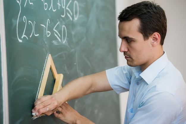 Молодой учитель или ученик нарисовать треугольник на доске с формулой