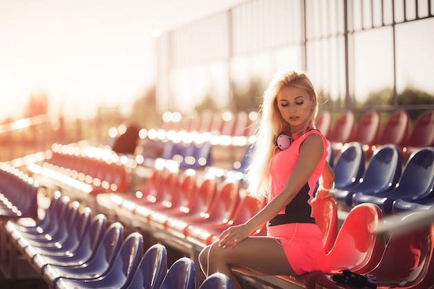 晴れた朝のトレーニングセッションの後休んで若い女性ランナー。