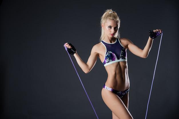 Фитнес женщина позирует со скакалкой. спортивная мотивация. идеальная женская посадка по фигуре.