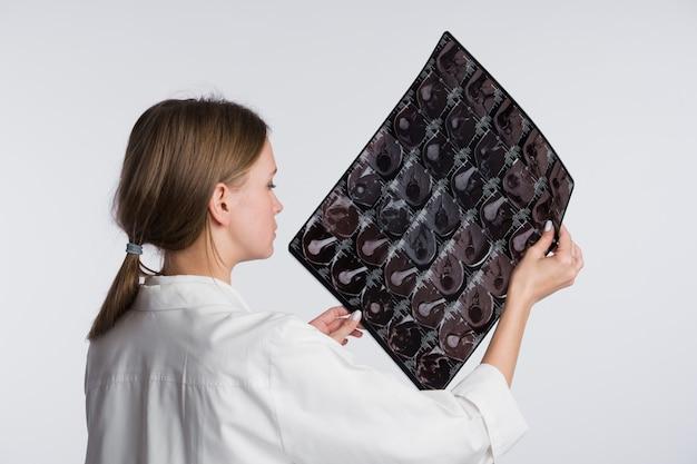 Женщина-врач изучения рентгеновского снимка, вид сзади