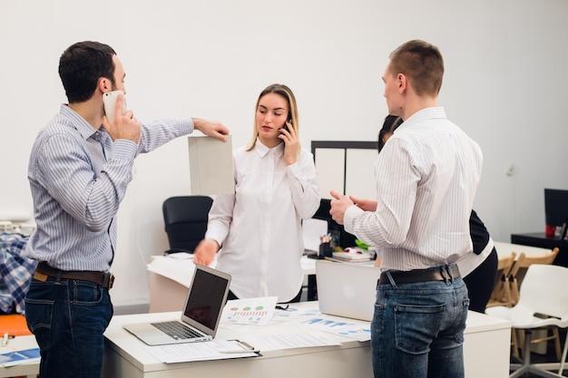 Группа из четырех разных веселых коллег, принимая автопортрет и делая смешные жесты руками в небольшом офисе