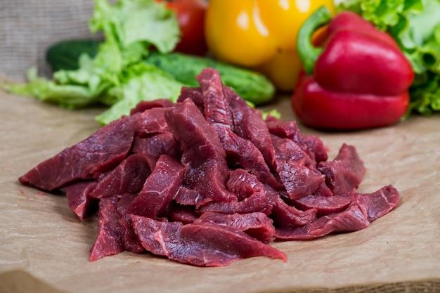 新鮮な生のみじん切りの牛肉、スパイス、ハーブの軽い木製テーブル