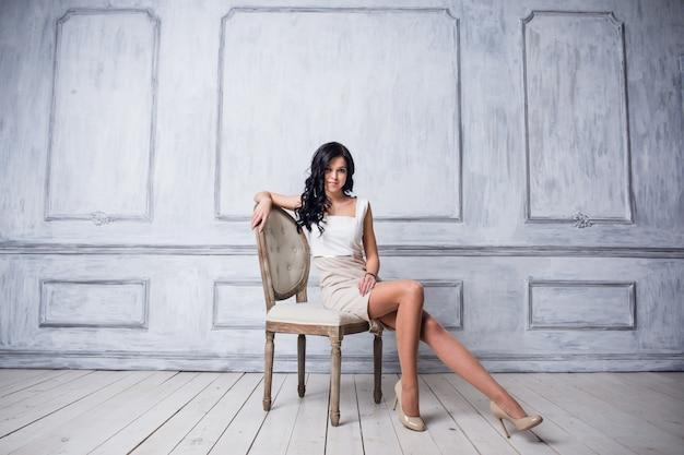 Портрет привлекательной молодой женщины, сидя в кресле.