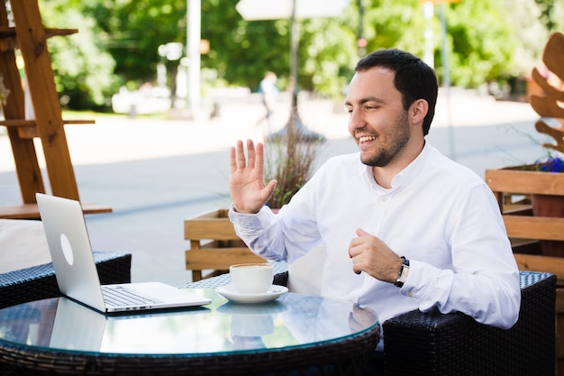 仕事とリラックス。オンライン会議。屋外のカフェでスカイプで話しているラップトップで作業するシャツに身を包んだ実業家