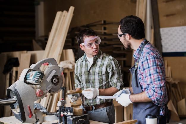 Двое мужчин строитель с циркулярной пилой беседуют