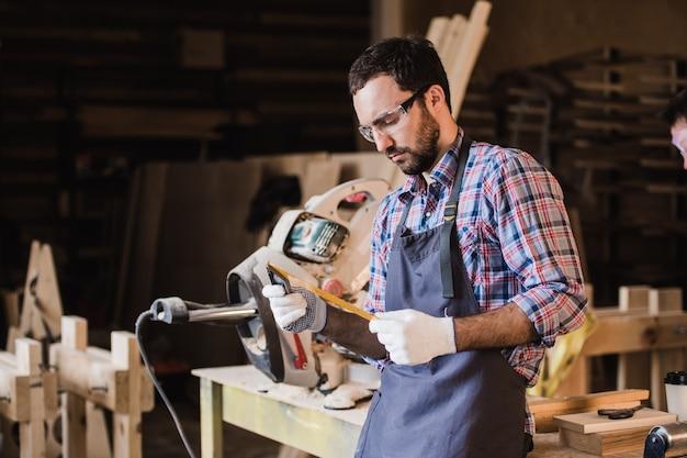 Красивый плотник в защитных очках стоит возле своего деревянного предмета в мастерской