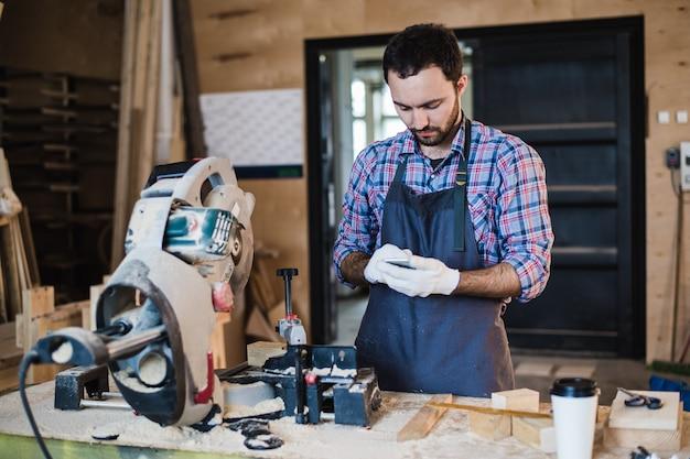 Карпентер пишет кому-то на своем смартфоне возле циркулярной пилы в пыльной мастерской