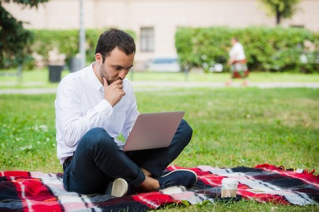 Человек работает с помощью ноутбука в парке. на улице, парень выглядит вызывающим и думающим
