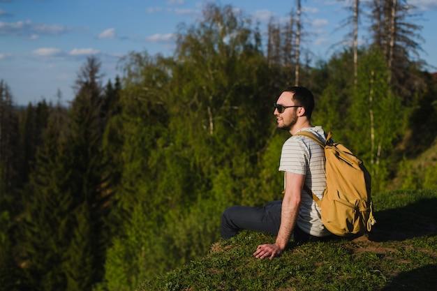 森の中で屋外のバックパックでハイキングを使用している人
