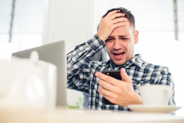 Усталый фрилансер использует мобильный телефон во время работы в кафе