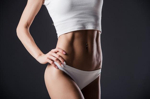 腰に手を当ててフィット女性の胴体のクローズアップ。黒い壁に完璧な腹部の筋肉を持つ女性