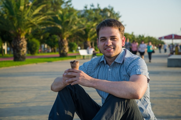 Счастливый красивый молодой человек ест мороженое на открытом воздухе