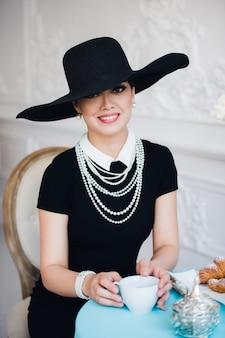 魅力的な女性は椅子に座って、黒のドレス、帽子、真珠を着ています。