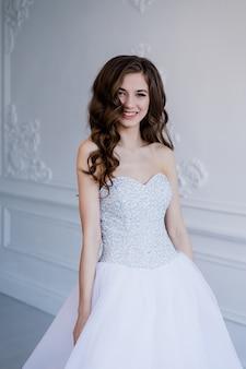 インテリアでウェディングドレスでポーズと笑顔の長い巻き毛を持つ美しい笑顔の花嫁の女性の肖像画を閉じます。美容室内ポートレート。