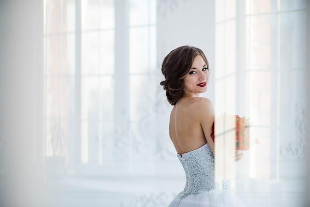 リビングルームの白いドレスの花嫁の若くて美しいファッションアート写真。ガラスのドアを通って撮影され、光の創造的な反射がポートレートをオーバーレイします。