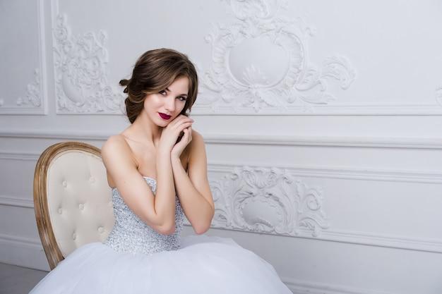 美しい花嫁の肖像画。結婚式の装飾、ドレス、白い背景
