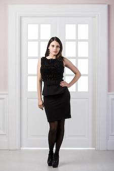 Полноразмерная фотомодель черного платья позирует в студии лофт, интерьер дома, двери позади