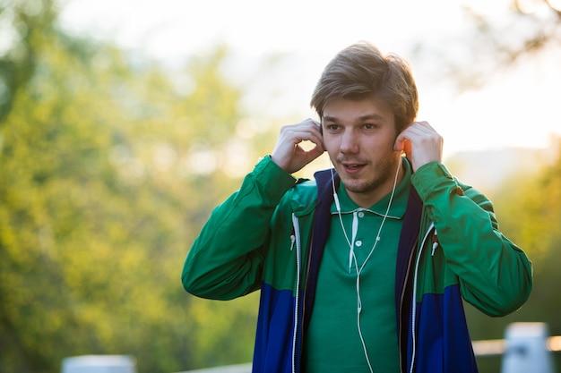日没でインイヤーヘッドフォンで音楽を聴いて街を歩いて一般的な若い男。柔らかく暖かい光。