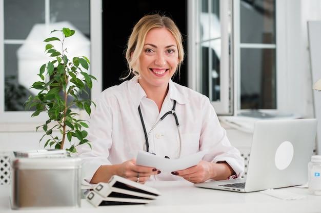 ミッドアダルト女性医師のオフィスの机で文書を読む