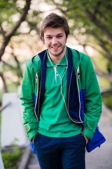 ハンサムな男が街を歩いて笑顔で公園で音楽を聴きます。柔らかい夕日の光。