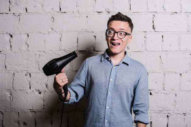 Молодой сумасшедший стильный мужчина с парикмахером и смешные выражения на серой кирпичной стене
