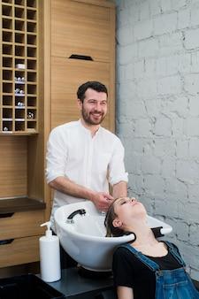 美容院で若い女性に頭を洗うヘアスタイリスト