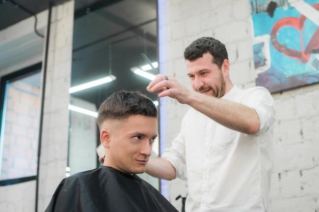 プロのスタイリング。理髪店で電気かみそりで美容院で散髪をして満足している若者の側面図を閉じる