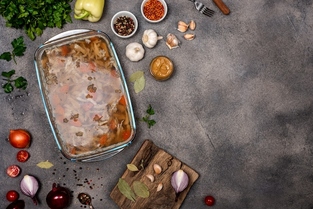 Домашнее желе с мясом. засолка из птицы и говядины, традиционное русское и украинское блюдо на сером фоне с горчицей. копировать пространство