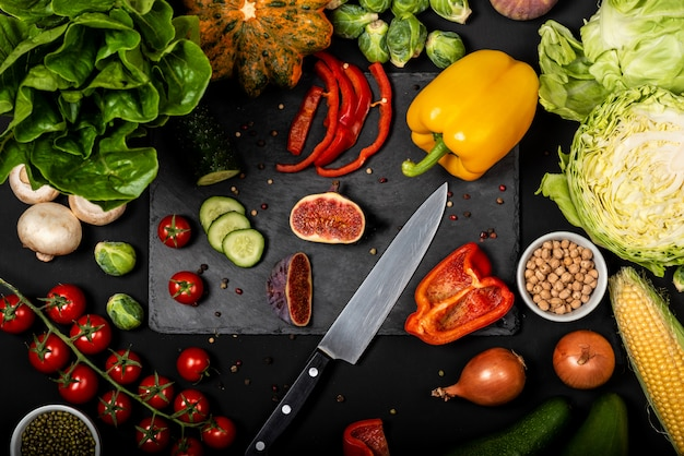 Различные свежие овощи на черном фоне. здоровая вегетарианская еда. вид сверху.