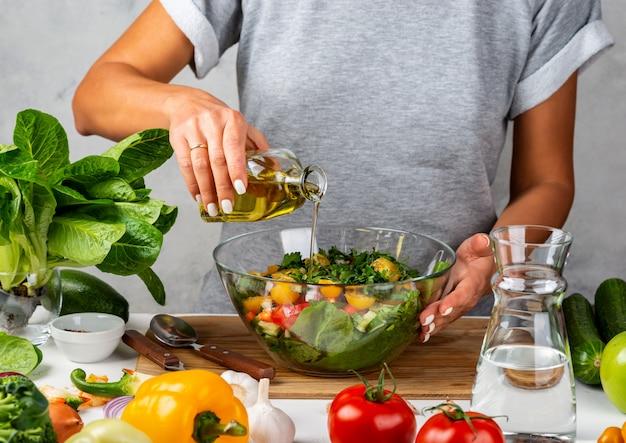 Женщина наливает оливковое масло из бутылки в салат в стеклянную емкость. готовим на кухне. концепция здорового питания.