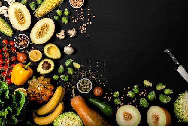 黒い背景にさまざまな野菜のセット。コピースペースを持つトップビュー。