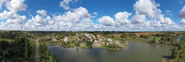 湖の近くの丘の上の美しい村の風景の空撮。丘の上の村の中心には、古い美しい教会があります。美しく神秘的で妖艶な雲が村の上を流れる