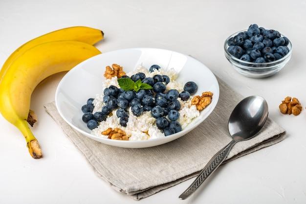 Здоровый завтрак. творог с черникой, орехами, медом и мятой в белой миске