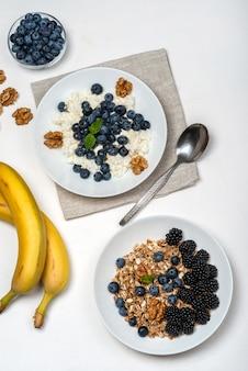 Здоровый завтрак. творог с черникой, орехами, медом и мятой в белой миске вид сверху.