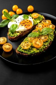 Открытые бутерброды с авокадо гуакамоле, желтые помидоры черри, жареные яйца и базилик на черной тарелке. здоровая еда или закуска