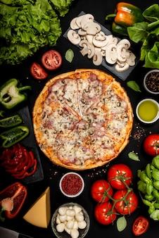Домашняя пицца готова к употреблению с сырьем. вид сверху .
