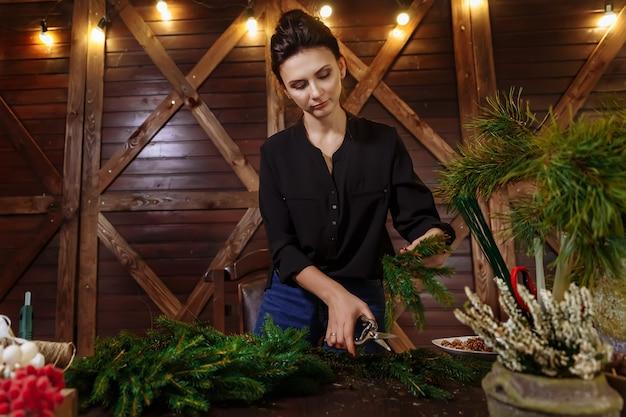 クリスマスリースで働く花屋の女性。