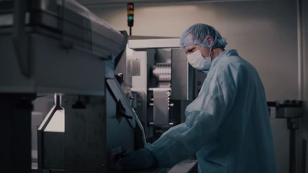 エンジニア制御医薬品製造、製薬機器を操作する工場労働者、薬局業界、工場労働者プログラミング制御製造ライン。
