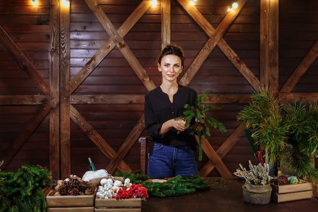 クリスマスの花輪、クリスマスの常緑樹の花輪を準備する若いかわいい笑顔の女性デザイナーと働く花屋女性。