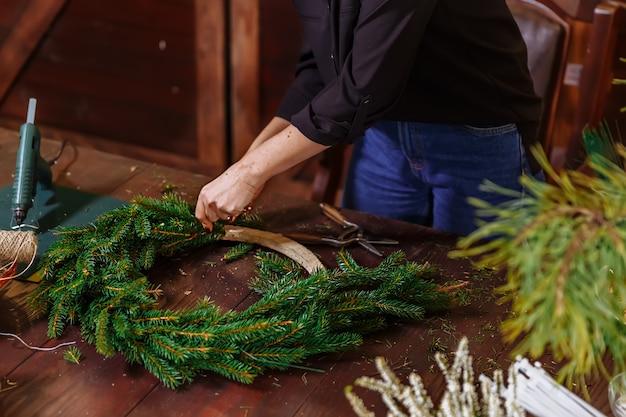 クリスマスの常緑樹の花輪、自分の手でクリスマスの装飾のメーカー、休日のクリスマスリース、新年のお祝いを準備する若いかわいい笑顔の女性デザイナー。