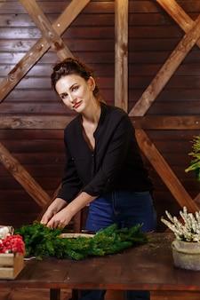 Женский флорист украшая рождественский венок в цветочном магазине, женщина, делающая украшения для рождественских праздников, делающая обстановку для праздника.