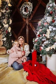 メリークリスマスと新年あけましておめでとうございます、ママと娘は屋内でクリスマスツリーを飾る