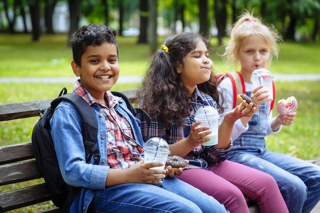 Смешанная расовая группа школьников едят обед вместе на перерыв на открытом воздухе возле школы.