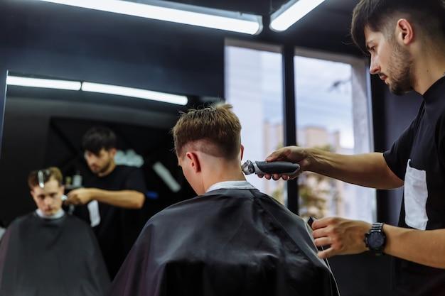 電気かみそりで男性の散髪。理容師は、ヘアクリッパーを使用して、理髪店でクライアントのヘアカットを行います。電気シェーバーで理髪男。