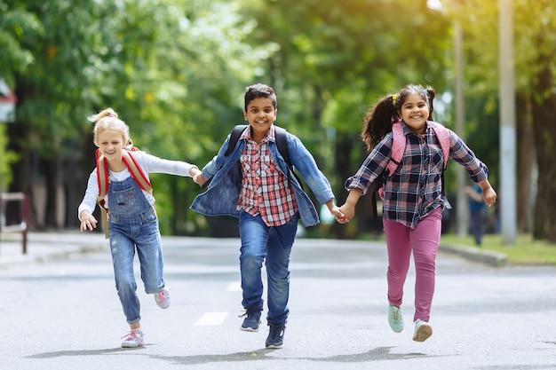 Обратно в школу. смешанная расовая группа счастливых студентов начальной школы с рюкзаками работает держаться за руки на открытом воздухе. концепция начального образования.