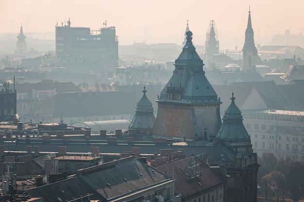 ハンガリー、ブダペストの歴史的な市内中心部の霧の屋上ビュー